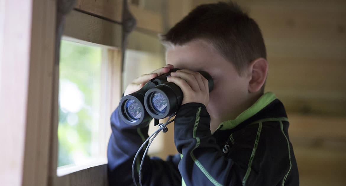 Boy looking through binoculars.