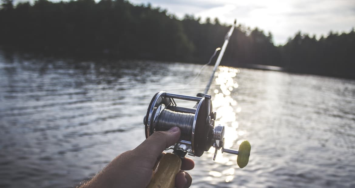 Hand holding a fishing rod on a river.